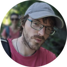 A circular portrait picture of a man with a grey baseball cap and stubble. He appears to be on a hike with someone behind him, though the background is blurred.